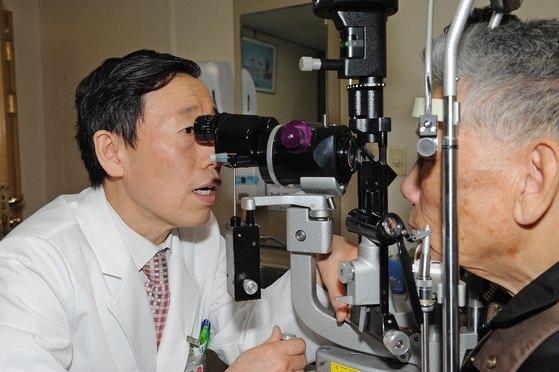 김응권 연세대 세브란스병원 안과 교수가 각막 질환을 앓는 노인 환자의 눈을 검사하고 있다. [사진 세브란스병원]