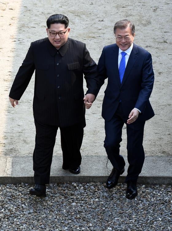 """김정은 북한 국무위원장이 27일 정전협정 65년 만에 북한 최고지도자로는 처음 남으로 왔다. 그를 맞은 문재인 대통령이 '나는 언제쯤 (북으로) 갈 수 있겠느냐""""고 하자 김 위원장이 문 대통령의 손을 잡고 군사분계선 북쪽으로 넘어갔다가 돌아오며 웃고 있다. [김상선 기자]"""