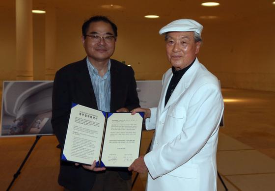 2013년 8월 8일, DDP에서 공동전시 협약을 체결할 당시의 전성우 간송미술문화재단 이사장(오른쪽)과 백종원 서울디자인재단 대표. [중앙포토]