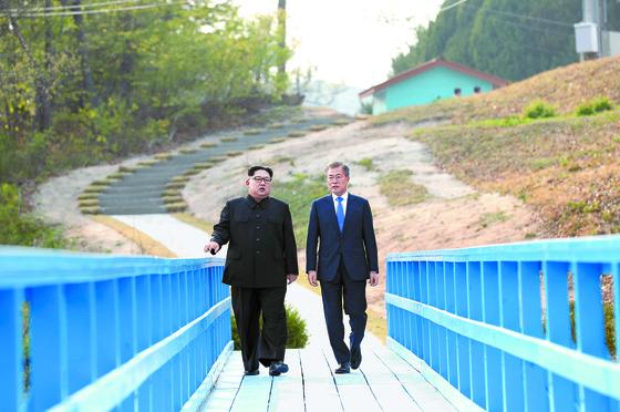 문재인 대통령과 김정은 북한 국무위원장이 공동 식수를 마친 뒤 군사분계선 표식물이 있는 '도보다리'까지 산책을 하며 담소를 나누고 있다. 두 정상은 이날 배석자없이 44분간 회담했다. [청와대사진기자단]