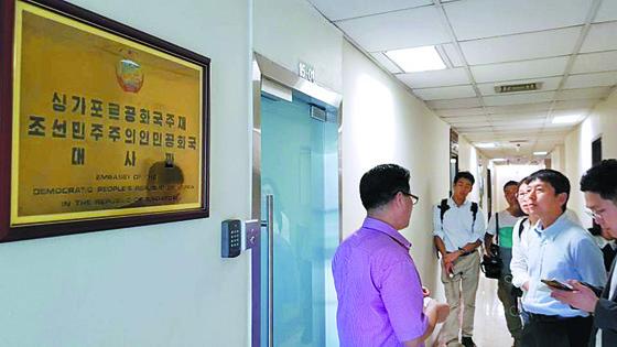 북·미 정상회담이 다음달 12일로 예정되자 많은 기자가 싱가포르 주재 북한대사관을 찾았다. 북한대사관의 1등 서기관(왼쪽)이 11일 사무실 앞에서 국내외 기자들의 질문에 답변하고 있다. [연합뉴스]