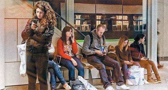 런던의 역에서 볼 수 있는 일상적인 풍경. 스마트폰에 중독된 사람들이 늘고있다. '고독한 군중'의 시대가 저물고 '함께 외로운' 시대가 개막했다. MIT 터클 교수는 대화가 공감 능력과 생산성 향상에 필수적이라고 역설한다. [사진 dksesh]