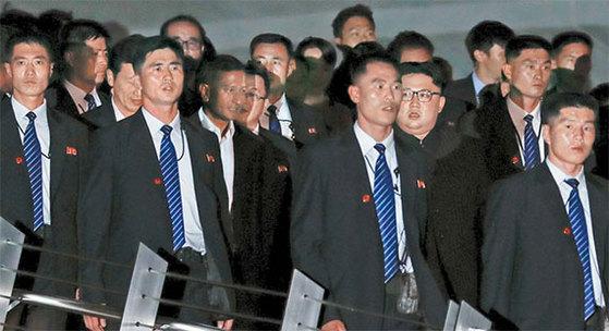 김정은 북한 국무위원장이 11일(현지시간) 싱가포르 메르리온 파크를 방문했다. 북한 경호원들이 김 위원장을 에워싼 채 이동하고 있다. [로이터=연합뉴스]