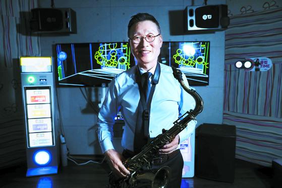 TJ 미디어의 신형 노래방 기기 앞에서 윤재환 회장이 색소폰 연주를 연습하고 있다. [김경빈 기자]