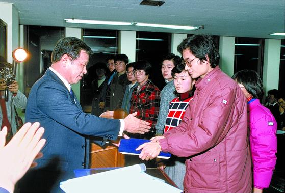고 최종현 회장(왼쪽)이 1986년 해외 유학을 앞둔 한국고등교육재단 장학생들에게 장학증서를 전달하고 있다. [사진 SK]