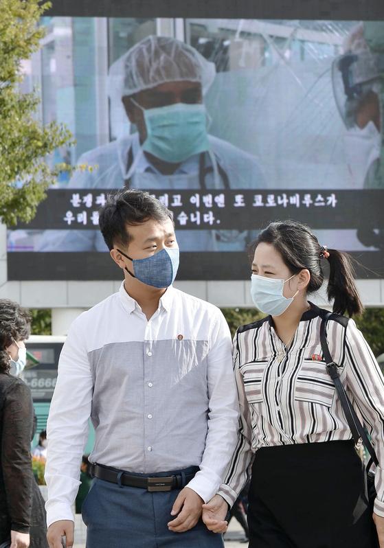 북한 평양역 앞을 마스크를 쓴 남녀가 걸어가고 있다. 이들의 뒤에 있는 대형 모니터에는 세계 코로나19 감염 상황을 전하는 영상이 비치고 있다.〈사진=연합뉴스〉