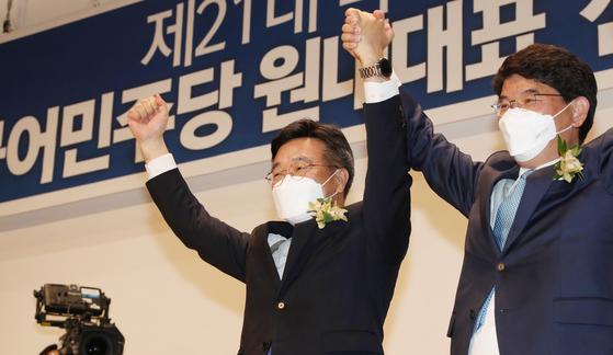 윤호중 더불어민주당 신임 원내대표(왼쪽)가 함께 경쟁했던 박완주 의원와 손을 들어 인사하는 모습 〈출처=연합뉴스〉