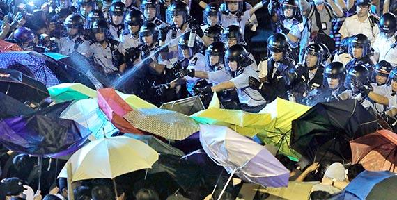 중국으로부터 홍콩의 독립을 지지하는 시민 1만3000명이 지난 6일 홍콩 시내에서 시위 도중 경찰이 쏘는 최루액을 우산으로 막고 있다. [홍콩 AP=뉴시스]