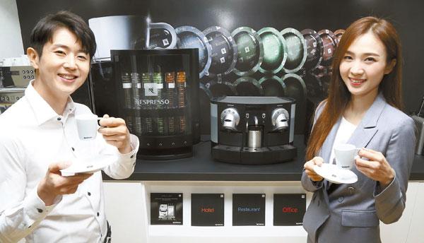 지난 10일 서울 삼성동 코엑스에서 열린 '2016 서울 카페쇼'를 찾은 직장인들이 네스프레소의 기업용 캡슐커피머신에서 뽑은 커피를 마시고 있다.