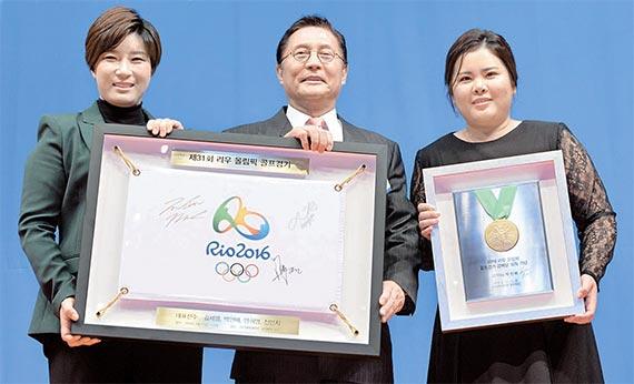 """박세리 감독(왼쪽), 허광수 대한골프협회 회장(가운데)과 올림픽 금메달리스트 박인비가 '골프인의 밤' 행사에서 기념촬영을 하고 있다. 이날 포상금 3억원 증서를 받은 박인비는 올림픽 금메달을 들어보였다. 허광수 회장은 """"한국 여자골프는 리우 올림픽에서 금메달을 따내 국위 선양에 기여했다""""고 말했다. [뉴시스]"""