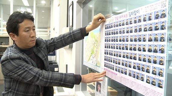 한정일 경위가 서울 강동경찰서 성내지구대 벽에 수어(手語) 포스터를 붙이고 있다. [사진 강동경찰서]