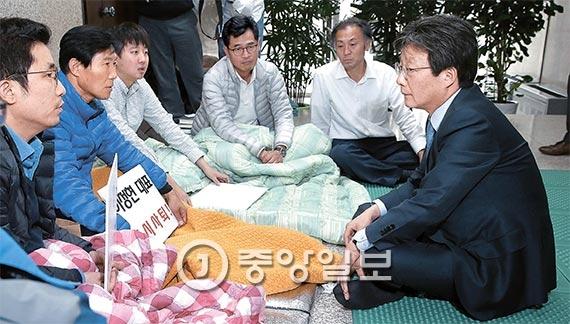 새누리당 유승민 의원(오른쪽)이 18일 오후 이정현 대표의 사퇴를 요구하며 국회 당 대표실 앞에서 단식 중인 원외 당협위원장들을 만났다. [사진 박종근 기자]