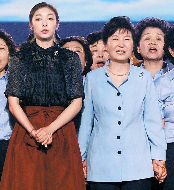 김연아(왼쪽)가 지난해 8월 광복 70주년 국민대합창 행사에서 박근혜 대통령과 함께 애국가를 부르고 있다. 김연아는 당시 박 대통령이 잡은 손을 슬며시 놓고 시선을 피해 논란을 일으켰다. [뉴시스]