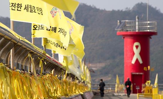 지난 21일 진도 팽목항을 찾은 추모객들이 박 대통령 퇴진 등의 내용을 담은 리본과 깃발 주변을 지나고 있다. [프리랜서 오종찬]