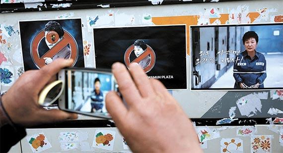 광화문 집회 참가자가 경찰버스에 붙어 있는 박근혜 대통령 비판 스티커를 휴대전화 카메라로 찍는 모습. [로이터=뉴스1]