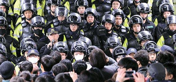 12일 3차 촛불집회에서 마주 선 경찰과 시위대. 이들 사이엔 팽팽한 긴장감이 돌게 마련이다. 그러나 최순실 국정 농단을 둘러싼 촛불집회는 다르다. 시민은 한결같이 평화를 외친다. 직무상 입을 열지 못하는 경찰은 그저 묵묵히 그 자리를 지킨다. [뉴시스]
