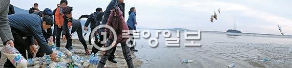지난달 30일 오후 인천시 강화군의 한 섬에서 탈북자들이 쌀을 넣은 페트병을 바다로 던지고 있다. 페트병은 조류를 따라 황해도로 흘러간다. 스마트폰 파노라마 기능으로 촬영해 사람 일부가 일그러졌다. [사진 김춘식 기자]