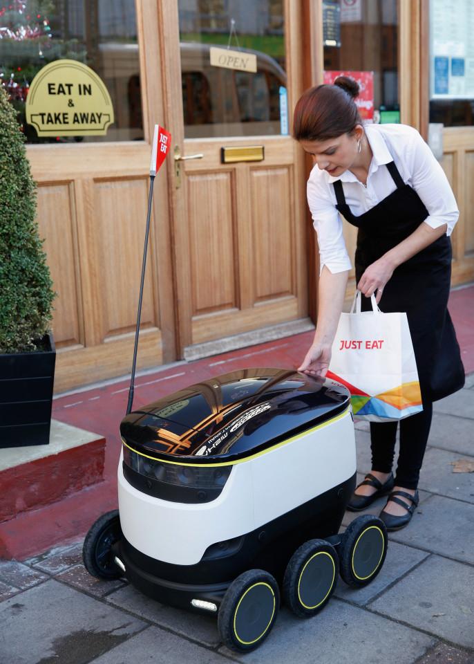 음식점에서 주문한 음식을 로봇에 실고 있다.  [사진 저스트잇]