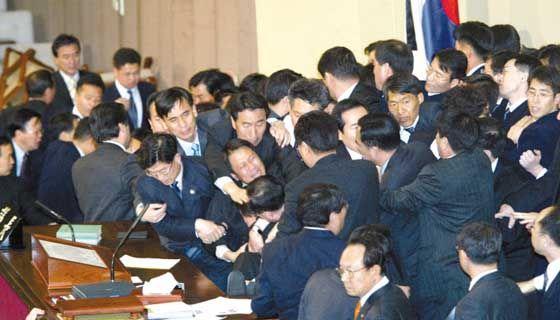 2004년 3월 노무현 대통령에 대한 탄핵 표결 당시 국회 본회의장 단상에서 몸싸움을 벌인 여야 의원들. 노 전 대통령 탄핵안은 전체 의원 271명 중 193명의 찬성으로 가결됐다.[중앙포토]