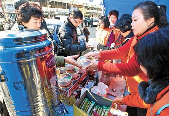 8일 서문시장 화재현장에서 자원봉사자들이 컵라면과 커피를 상인들에게 건네고 있다. [프리랜서 공정식]