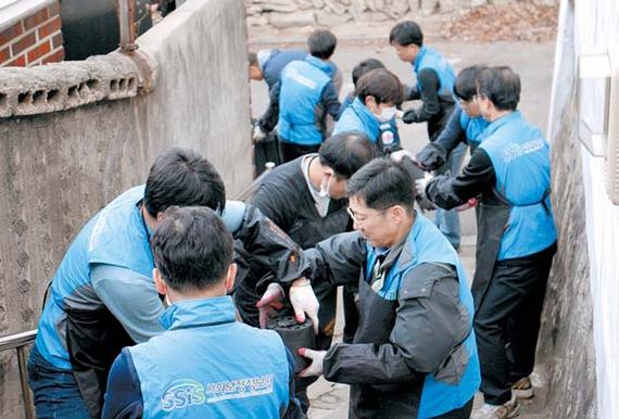 지난 2일 서울 성북동에서 사회보장정보원 임직원들이 저소득 가구에 연탄을 배달하고 있다.