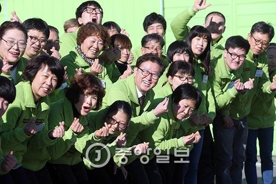 김만석 사장(가운데 안경 쓴 이)이 직원들과 함께 웃고 있다. 태건상사는 직원 98명 중 48명이 장애인으로, 폐자재를 활용한 전기부품 생산업체답게 유니폼도 '친환경'을 의미하는 녹색으로 맞췄다. [사진 최정동 기자]