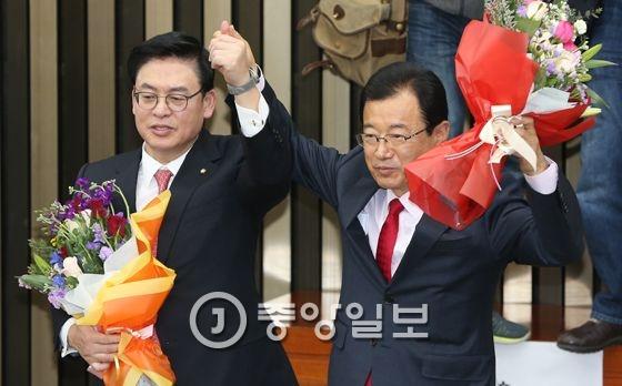 새누리당 정우택 새 원내대표(왼쪽)와 이현재 정책위원장이 16일 오전 국회에서 열린 의원총회에서 손을 들어 당선 인사를 하고 있다. 강창광 기자