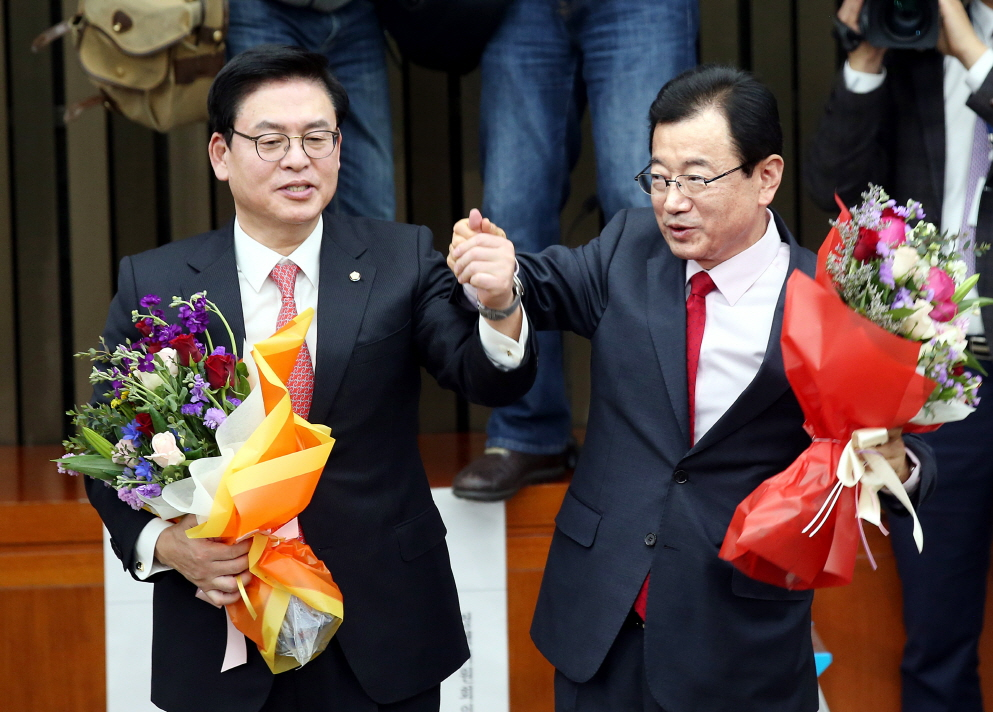 지난 16일 정우택 새누리당 신임 원내대표(왼쪽)가 이현재 신임 정책위원장이 당선된 뒤 함께 축하 꽃다발을 들고 기념사진을 찍고 있다.