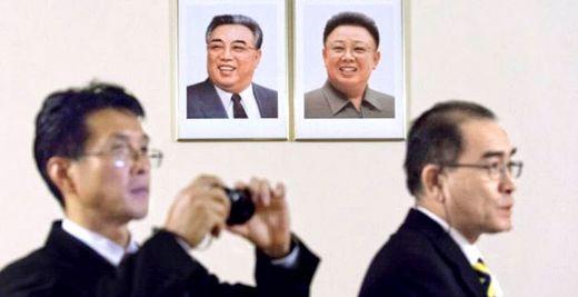 영국 주재 북한 대사관에서 근무하던 태영호 공사(오른쪽)가 김일성과 김정일 초상화 앞에 서있다. [사진 BBC 캡처]