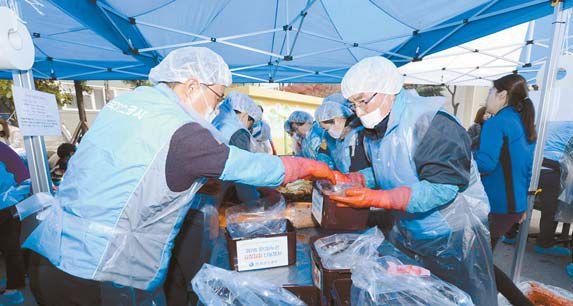 한국가스공사가 지난 11월 30일 개최한 사랑의 김장김치 나눔 행사에서 이승훈 사장(오른쪽)이 직접 담근 김치를 통에 담고 있다. [사진 한국가스공사]