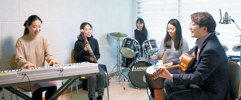 이화여대 일반대학원 음악치료학과 이진형 교수(맨 오른쪽)와 학생들이 기타·키보드·타악기 등으로 즉석 연주를 하고 있다. [프리랜서 조상희]