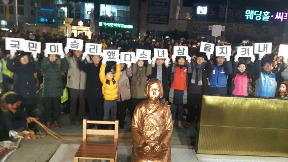 31일 오후 9시 부산시 동구 일본 영사관 앞에 설치된 평화의 소녀상 주위에서 부산 시민들이 `국민이 승리했다. 소녀상을 지켜내자`라는 피켓을 들고 있다. [사진 부산경찰청]