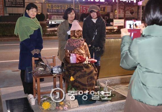 6일 오후 일본 정부가 부산 일본영사관 앞에 설치된 위안부 소녀상과 관련해 전방위 압박에 나선 가운데 시민들이 부산 영사관 앞에 설치된 소녀상에서 기념촬영을 하고 있다. 송봉근 기자