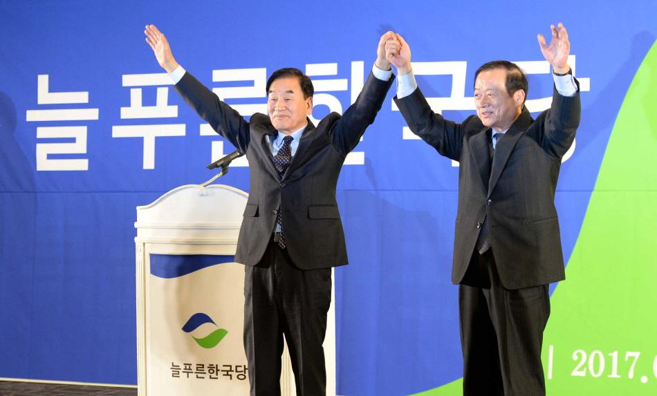 11일 오후 서울 종로구 세종문화회관 세종홀에서 열린 늘푸른한국당 창당대회에서 이재오와 최병국 공동대표가 손을 잡고 인사를 하고 있다. [뉴시스]