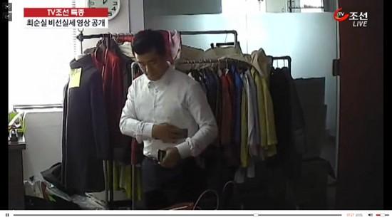 이영선 청와대 행정관이 최순실씨의 휴대전화기를 자신의 셔츠에 닦는 모습. 그는 이 전화기를 최씨에게 건넸다. [사진 TV조선 캡처]