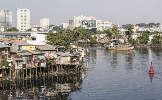 베트남 호치민시 사이공강의 모습. 호화로운 '비텍스코 파이낸셜 타워'앞쪽으로 도시 빈민들이 거주하는 수상가옥들이 즐비하다.