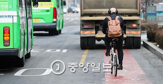 17일 자전거를 탄 시민이 서울 지하철 여의도역 주변 자전거 도로를 이용하고 있다. 자전거만 진입해야 하는 도로에 주차된 덤프 트럭이 길을 막고 있다. [사진 김경록 기자]