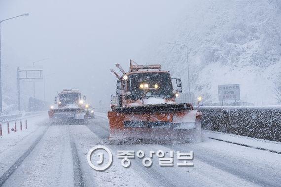 영동고속도로 대관령 구간에 폭설이 쏟아지는 가운데 제설차량 두 대가 도로에 쌓인 눈을 치우고 있다.