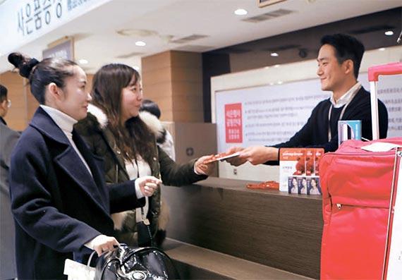 서울 소공동 롯데백화점 본점에서 중국인 관광객이 사은품을 받고 있다. [사진 롯데백화점]