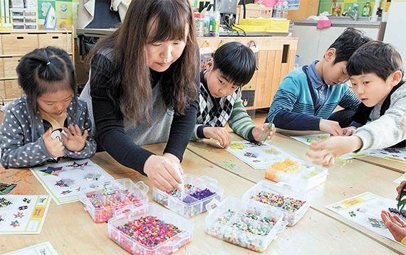 지난 13일 전남 장성군 진원면 진원초등학교에서 학생들이 천경주 돌봄전담 강사와 함께 작은 구슬을 재료로 팽이를 만들고 있다. [프리랜서 오종찬]
