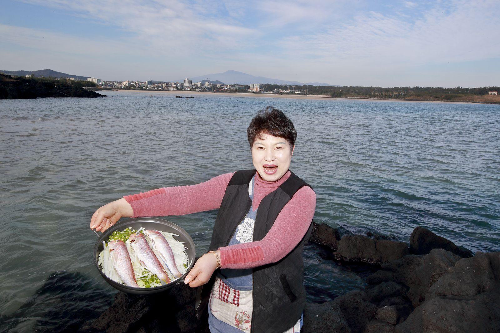 표선어촌식당 송금산(45) 사장이 제주 바다를 배경으로 옥돔국 재료들을 들어보이고 있다.