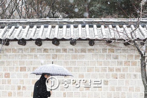 눈 내리는 덕수궁 돌담길을 한 시민이 지나가고 있다. 김경록 기자