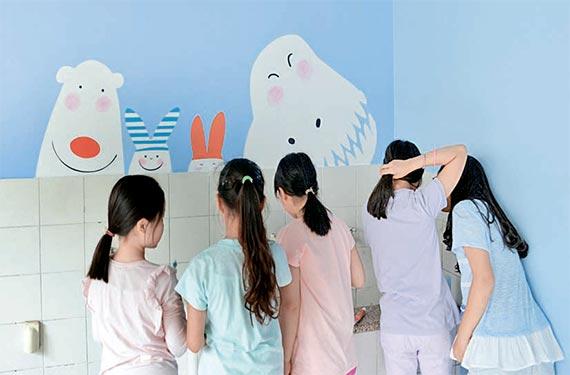 서울의 한 초등학교 학생들이 학교 벽면에 그려진 다양한 동물 캐릭터를 보며 이야기를 나누고 있다.