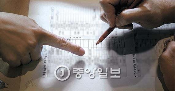 청춘희년네트워크 관계자가 '청년부채 제로 프로젝트'에 참가한 이모(32·여)씨가 작성한 지난달 지출내역서를 보면서 이행 상황을 점검하고 있다. [사진 김상선 기자]