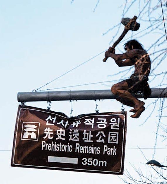 24일 대구 선사유적공원 인근 도로표지판 위에 설치된 원시인 조형물.