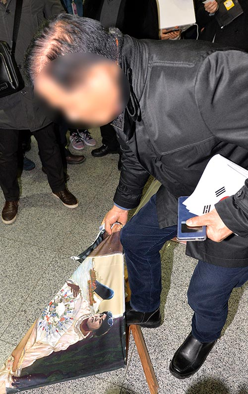 박근혜 대통령을 풍자한 누드 그림이 서울 여의도 국회에 전시돼 논란이 일고 있다. 한 박 대통령 지지자가 24일 오후 국회 의원회관에 전시된 이구영 작가의 그림 '더러운 잠'을 훼손하고 있다. [뉴시스]