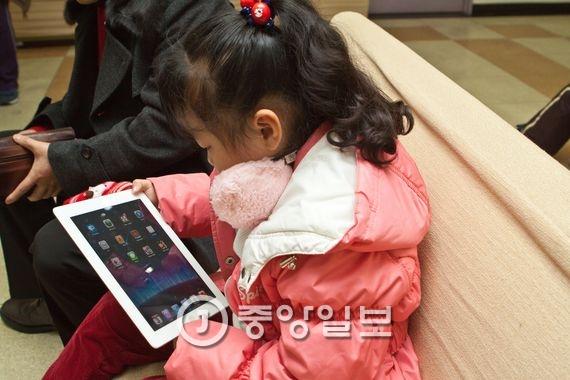 태블릿 PC 화면을 보고 있는 한 어린이. [중앙포토]