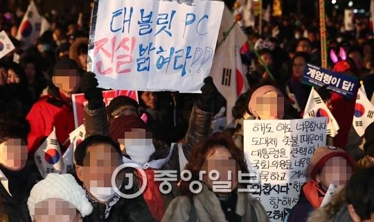 보수단체 회원들이 박근혜 대통령 탄핵 반대 집회에서 태블릿PC가 조작됐다고 주장하는 피켓을 들고 있다. [중앙포토]