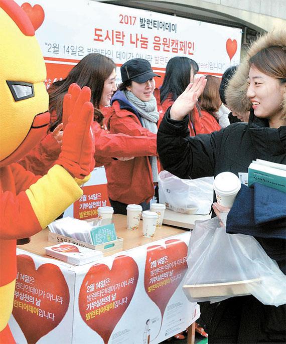 서울 노량진 학원가에서 14일 한 공시생이 '아이언맨' 인형 옷을 입은 대학생 자원봉사단 'V원정대' 소속 학생과 하이파이브를 하고 있다. V원정대는 이날 수험생들에게 도시락 500개를 선물했다. [뉴시스]