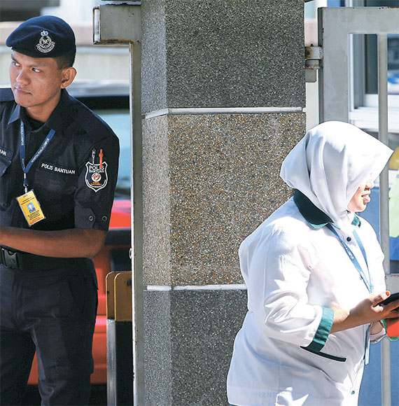 김정남의 시신이 안치된 말레이시아 쿠알라룸푸르 병원 앞에서 17일 경찰관이 출입을 통제하고 있다. 북한이 먼저 시신 인도 요청를 했으나 둘째 부인인 이혜경씨도 중국을 통해 시신 인수에 나섰다. [로이터=뉴스1]